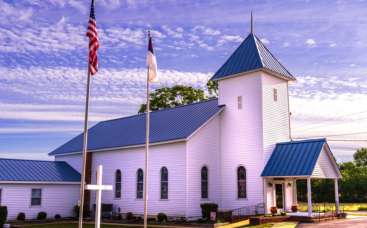 View of an Evangelical Church with the United States flag on the pole, and a clear blue sky